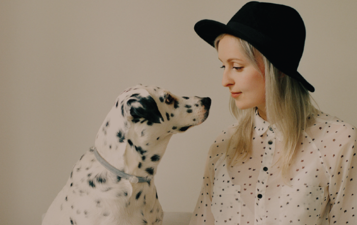 blonde woman in hat petting Dalmatian dog
