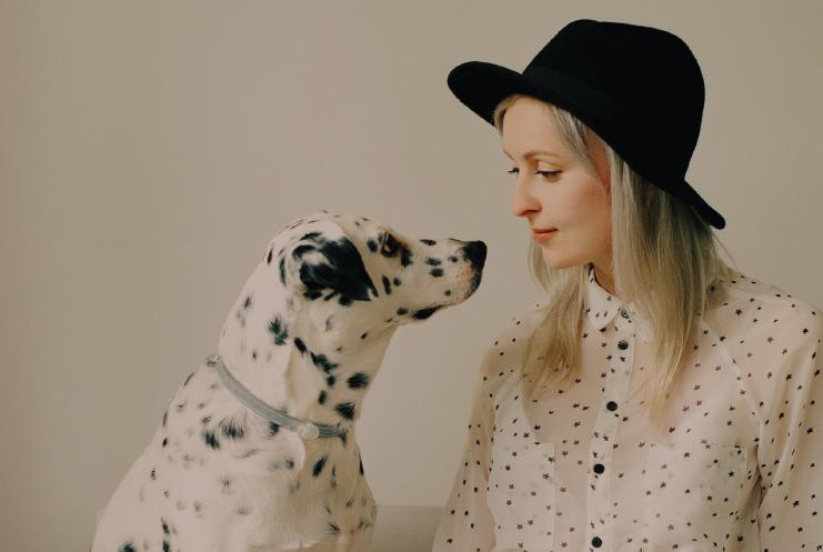 blonde woman in hat petting Dalmatian dog