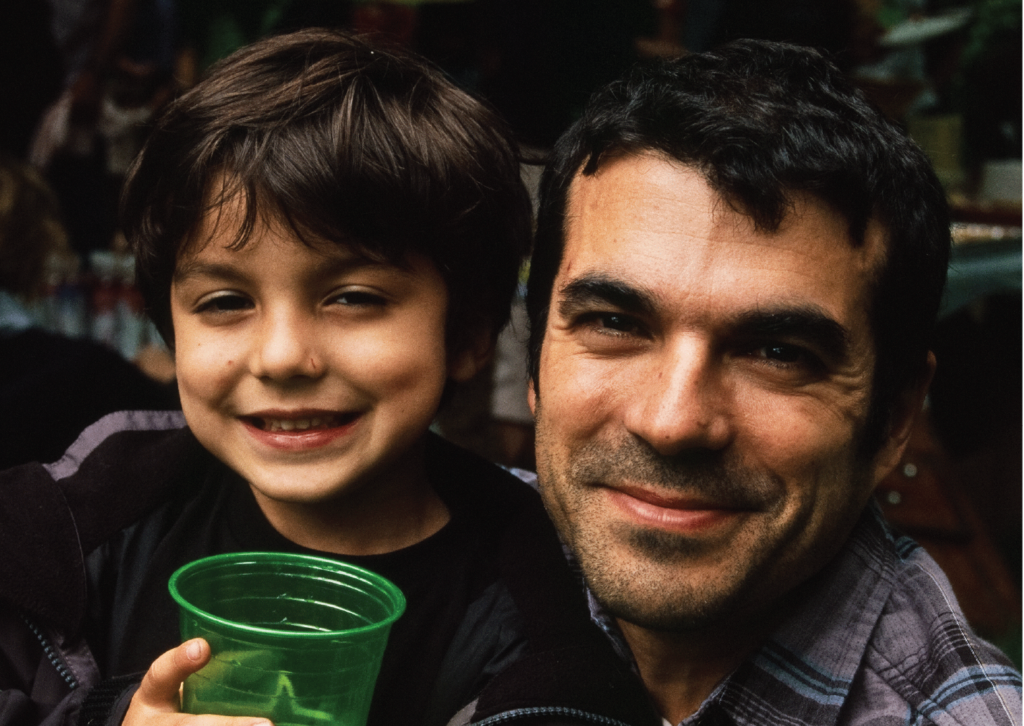 Jose Hernando and his son holding a green cup