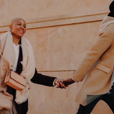 heterosexual couple walking outside in neutral fall clothing