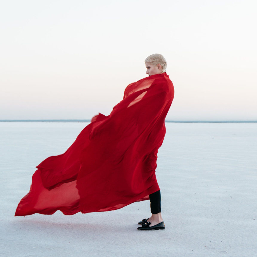 Woman Standing salt flats with fabric wrapped around her and blowing in the wind.
